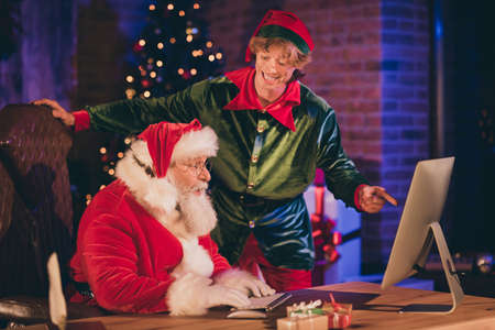 Photo portrait of elf pointing finger at desktop screen while santa claus sits surprised