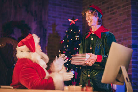 Photo portrait of elf handing santa claus a bunch of letters from children Stockfoto