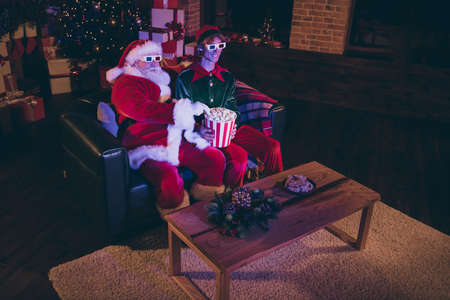 Photo portrait of santa claus taking popcorn from elfs lap watching movie on sofa in 3d glasses