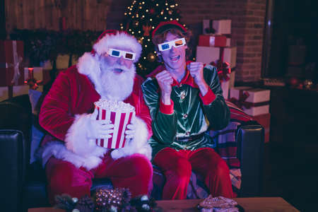 Photo portrait of santa claus and elf in anticipation holding popcorn watching movie on sofa in 3d glasses
