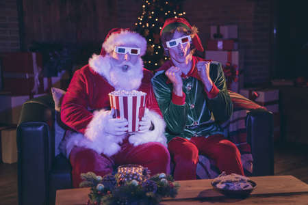 Photo portrait of shocked santa claus and elf holding popcorn watching movie on sofa in 3d glasses Stockfoto