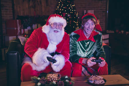 Photo portrait of santa claus and elf playing videogames holding controllers
