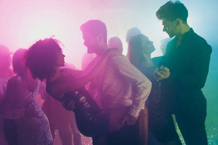 Photo of company many people two couple dance guy hold fancy lady leg neon shiny spotlight modern club indoors