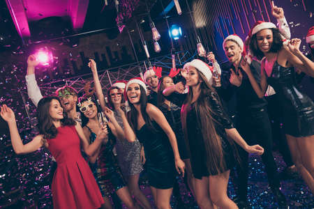 Photo of funny dreamy people meeting dance have fun hold glass wear mini dress x-mas headwear modern club indoors