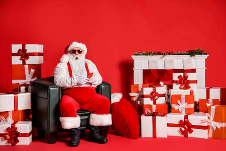 Portrait of his he nice attractive funky fat amazed stunned Santa father using device app 5g sitting in armchair isolated over bright vivid shine vibrant red color background