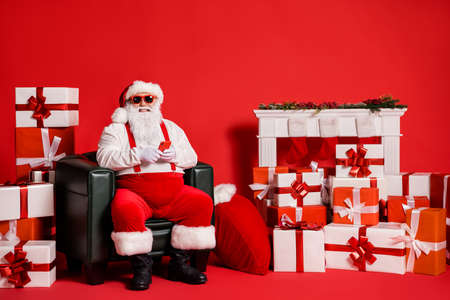 Portrait of his he nice attractive funky fat cheerful Santa using gadget blogging post sitting in armchair pile stack gifts order isolated bright vivid shine vibrant red color background Stock fotó