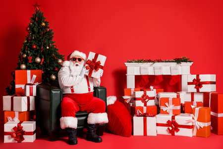 Portrait of his he nice attractive funky fat amazed wondered curious Santa sitting in armchair holding in hands giftbox isolated bright vivid shine vibrant red color background