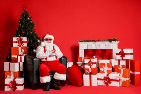 Portrait of his he nice attractive funky fat overweight cheerful Santa sitting in armchair drinking beverage in decorated room isolated bright vivid shine vibrant red color background