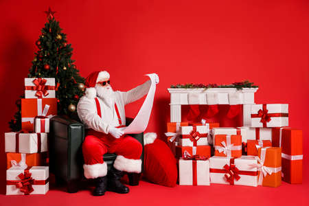 Portrait of his he attractive funky fat overweight Santa sitting in armchair decorated living-room reading long paper letter wishlist isolated bright vivid shine vibrant red color background