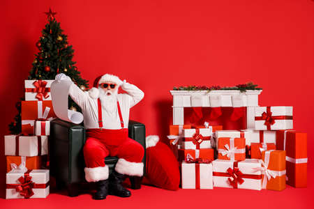 Portrait of his he attractive funky fat overweight stunned Santa sitting in armchair reading long paper letter gift list pile stack order isolated bright vivid shine vibrant red color background Stockfoto