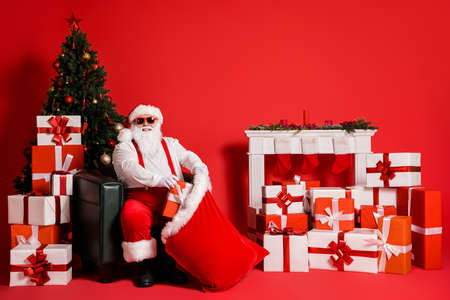 Portrait of his he attractive funky fat overweight cheerful glad Santa sitting in armchair packing giftboxes in sack North Pole delivery isolated bright vivid shine vibrant red color background Stockfoto