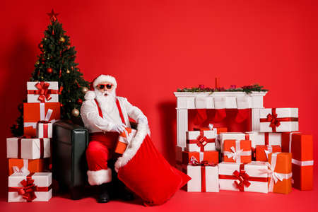 Portrait of his he attractive funky fat overweight amazed stunned Santa sitting in armchair decorated living-room packing giftboxes in sack isolated bright vivid shine vibrant red color background