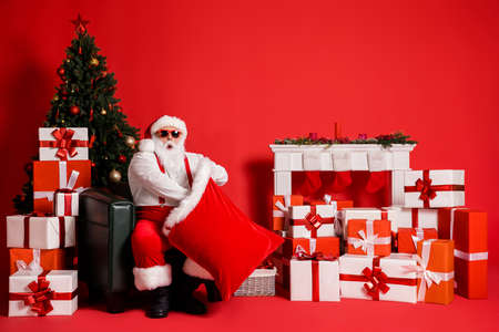 Portrait of his he attractive funky fat overweight amazed stunned Santa father sitting in armchair packing giftboxes in sack North Pole isolated bright vivid shine vibrant red color background