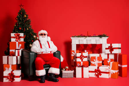 Portrait of his he attractive funky fat overweight cheerful Santa granddad sitting in armchair living-room christmastime day isolated bright vivid shine vibrant red color background