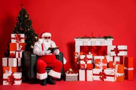 Portrait of his he attractive funky fat overweight amazed stunned Santa sitting in armchair living-room reading interesting book isolated bright vivid shine vibrant red color background