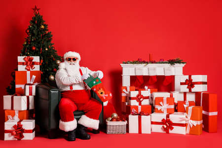 Portrait of his he attractive fat overweight funky cheerful cheery Santa sitting in armchair packing book for children festal day isolated bright vivid shine vibrant red color background