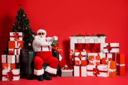 Portrait of his he attractive fat overweight funky amazed wondered Santa sitting in armchair packing gifts in sock christmastime isolated bright vivid shine vibrant red color background