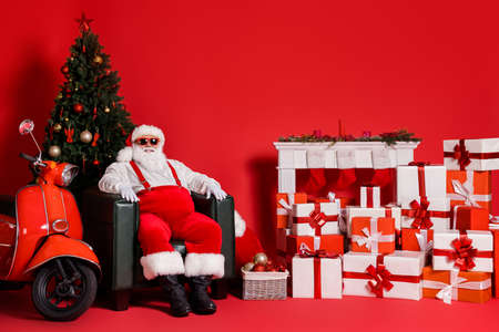 Nice attractive fat overweight cheerful Santa father sitting in armchair pile stack giftboxes around fast delivery holly jolly isolated over bright vivid shine vibrant red color background