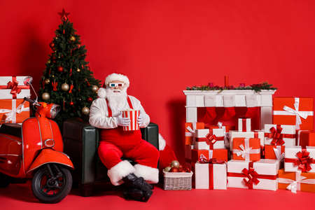 Full body photo of white hair santa claus hold pop corn box sit chair isolated on red bright color background with x-mas tradition decor Stockfoto