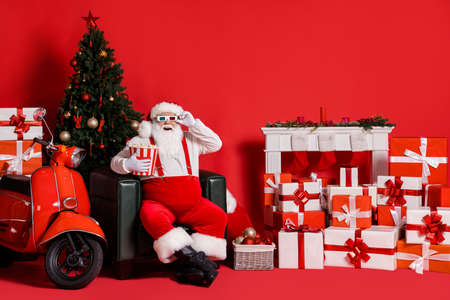 Full size photo of white hair santa claus hold pop corn box sit chair isolated on red bright color background with x-mas noel ornament Stockfoto
