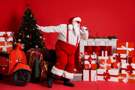 Full length photo of crazy santa claus sing pop song in mic isolated on red shine color background with x-mas fireplace chair gift box Stockfoto