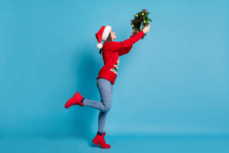 Full length body size of young girl wearing red xmas clothes hanging christmas handmade crafts green wreath made of christmas tree branches, decorative berries cones isolated on blue color background Stock Photo