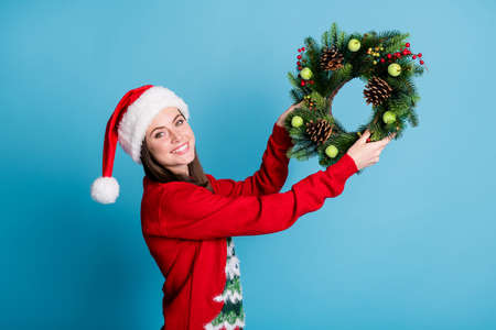 Portrait photo of girl wearing red xmas headwear hanging christmas handmade crafts wreath made of christmas tree branches decorative berries wooden cones isolated on blue color background Stock Photo