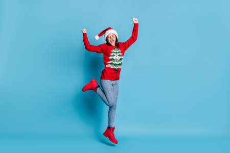 Full length photo of cute adorable lady jump raise hands fist leg open mouth wear santa x-mas headwear red ornamented pullover jeans boots isolated blue color background