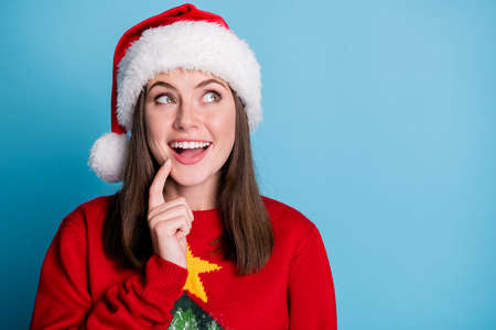 Photo of cute pretty lady beaming shiny smiling look up empty space open mouth finger cheekbone wear santa x-mas headwear red ornamented pullover isolated blue color background