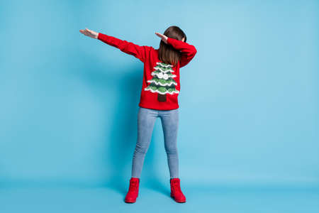 Full length body size photo of brunette girl wearing red xmas sweater dancing showing hype dab sign isolated on blue color background