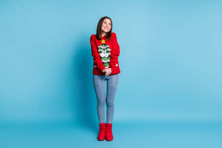 Full size photo of cute lovely girl in christmas tree decor sweater jumper look copyspace dream x-mas wish wear denim boots isolated over blue pastel color background