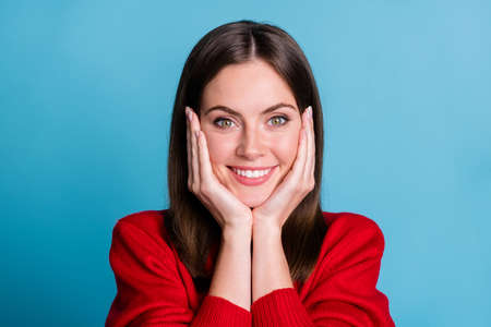 Close up photo of attractive adorable girl hold hands cheeks beaming smiling wear red soft comfy pullover isolated over blue pastel color background Stock Photo
