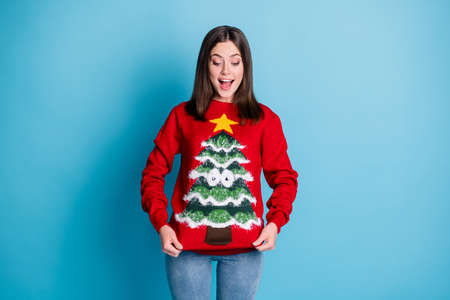 Photo portrait of surprised girl pulling ugly christmas sweater with hands smiling looking down isolated on pastel light blue colored background