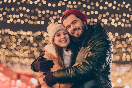 Photo of bonding boyfriend hug his affectionate girlfriend under x-mas christmas lights evening outdoors wear season coats scarf