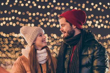 Photo of affectionate couple date on x-mas christmas under evening outdoors sky lights wear season coats headwear