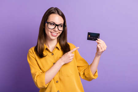 Photo of young pretty lady indicate finger look hold debit card wear spectacles yellow shirt isolated purple color background