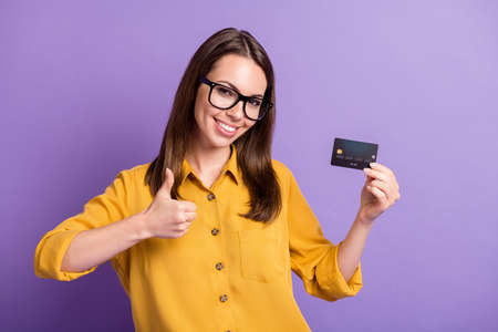 Photo of young lovely lady raise thumb up hold credit card wear eyewear yellow shirt isolated purple color background