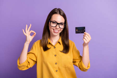 Photo of young lady raise hand show okey hold debit card toothy smile wear spectacles yellow shirt isolated purple color background Stock fotó