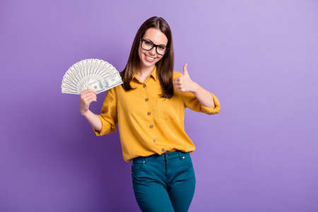 Photo of young girl raise thumb up hold fan cash money wear eyewear yellow shirt isolated purple color background Stock fotó