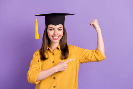 Photo of lovely lady indicate finger raise hand toothy smile wear yellow shirt college cap isolated violet color background