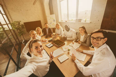 Photo of business people eight diversity age race colleagues sit table share anti crisis crash ideas team professionals making selfies teambuilding showing v-sign symbol office indoors Stock fotó