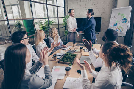 Photo of business people diversity colleagues sit table applauding partner anti crisis crash strategy plan professionals managed budget fail aged boss greets best team worker office indoors