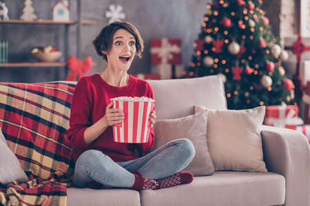 Photo of pretty young lady hold popcorn paper box sitting couch excited open mouth wear red pullover jeans socks indoors