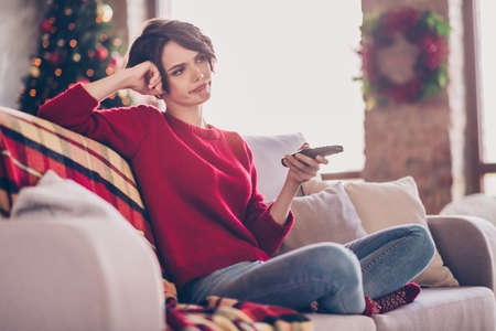 Photo of pretty bored young lady hold remote control hand fist head sitting sofa wear red sweater jeans socks indoors