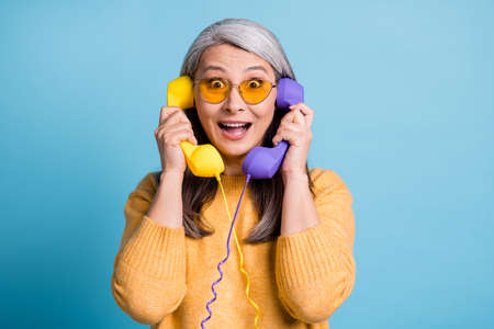 You cant be serious. Photo of charming excited old lady staring shocked look open mouth hold two phones listen new mall discounts sunglass yellow jumper vivid blue color background