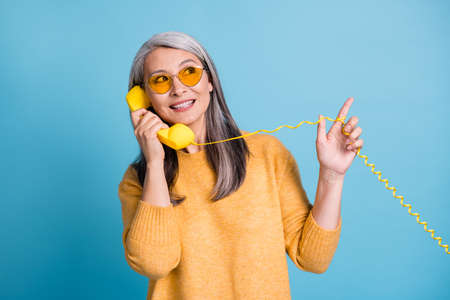 Photo of pretty charming aged woman calling friend ask new supermarket opened their street direct finger up playing wire wear sunglass yellow jumper vivid blue color background