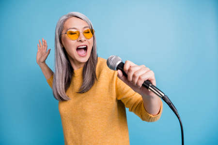 Close-up headshot photo of charming lovely singer old lady holding microphone open mouth close eyes singing last high notes chorus love song wear yellow jumper vivid blue color background