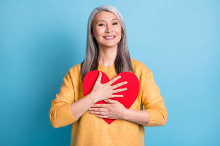 Photo of attractive cute aged woman white grey hairdo hands hold hug paper red heart shape receive valentine love yourself concept wear yellow pullover isolated blue pastel color background
