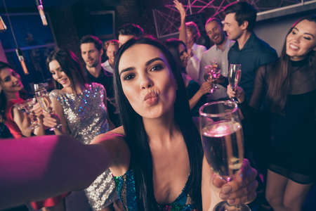 Self photo portrait of girl sending air kiss drinking champagne at luxury party Standard-Bild