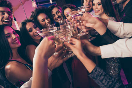 Close-up photo portrait of people drinking champagne cocktails clinking glasses at party